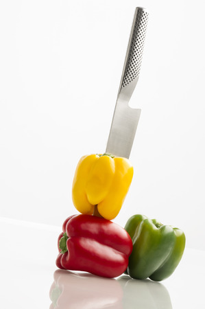 stainless steel kitchen: Three colourful sweet bell peppers in yellow, green and red pierced with a stylish stainless steel kitchen knife  Stock Photo