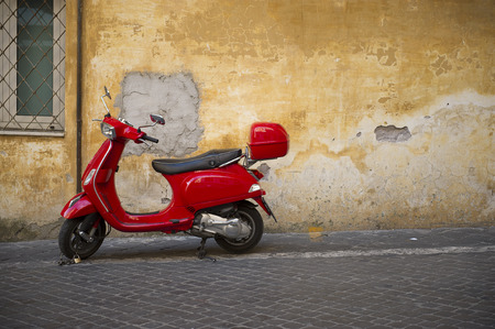 Bright shiny red Vespa scooter with a carrier parked on a sidewalk in front of a grungy dilapidated townhouse with peeling plaster on the wall and copyspace