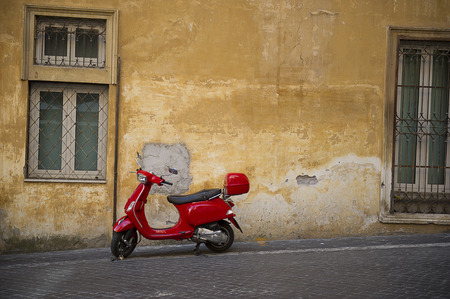 Bright red Vespa scooter parked in an urban street in front of a grungy old townhouse with burglar bars on the windows and crumbling plaster on the walls Stock Photo