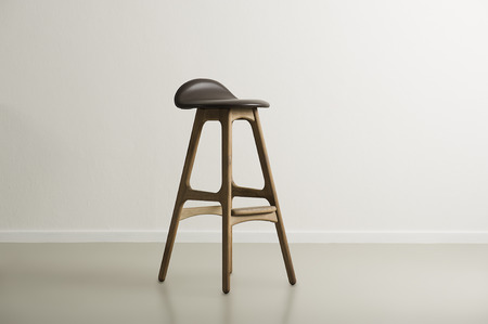 Wooden bar stool with a molded leather seat standing centered in a minimalist empty room with a white wall and copyspace, horizontal format photo