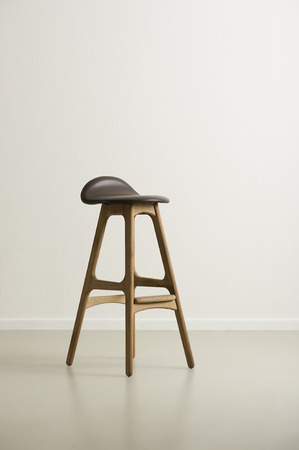 Moderrn high wooden bar stool with a black leather seat and footrests on a reflective floor in an empty room with a white wall, vertical format with copyspace in daylight photo
