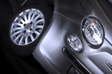spoked: Detail of the front headlight , parking light and tyre of a silver car with a spoked alloy sports wheel , close up low angle
