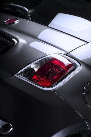 Detail van de boot en rode bekleding op het achterlicht van een kleine compacte hatchback auto, lage hoek close-up