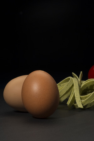 unbroken: Fresh hens eggs and dried tagliatelle pasta standing ready on a rustic kitchen counter to prepare a traditional Italian pasta dish, vertical format on a dark background with copyspace Stock Photo