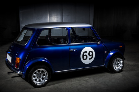 Iconic blue Mini Cooper , Austin or Morris, in a parking area with a 69 decal on the door, a popular economic two-door car introduced by BMC in the 1959 that went out of production in 2000