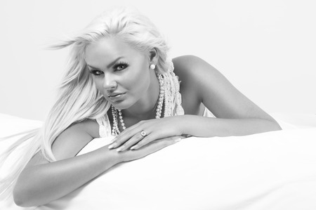 inscrutable: Beautiful glamorous blond woman wearing pearl necklaces and jewellery relaxing on her stomach on a bed looking sideways at the camera with a serious expression, greyscale portrait