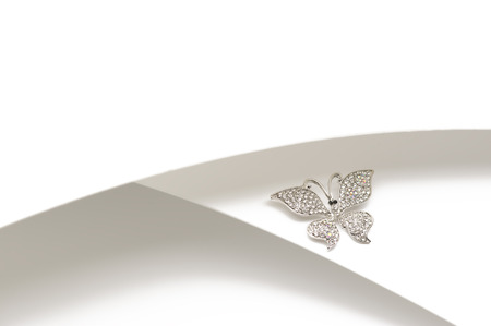 Elegant silver diamante butterfly ornament or brooch with outspread wings displayed on a two-tone silver and white background with copyspace