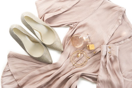 'evening wear': Outfit of stylish ladies clothing on a white background with elegant silver court shoes, gold bangles and a perfume bottle on a neutral tone dress or tunic for smart casual wear or evening wear