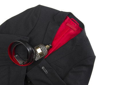 eveningwear: Stylish mens black or dark grey jacket with a colorful crimson lining and matching leather belt lying on a white background with a glass toiletry bottle, overhead view with copyspace