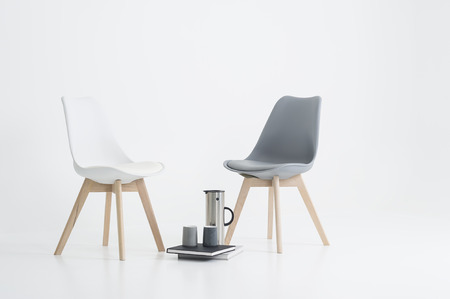Two modern chairs with a serving of coffee in a stylish flask with two mugs resting on hardcover books on the floor in between, over white