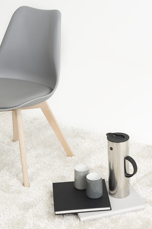 energizing: Serving of coffee alongside a modern molded chair with two empty mugs and an elegant tall flask resting on two hardcover books on a white carpet, with copyspace
