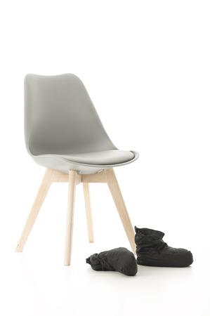 Conceptual Wooden Leg Chair and Black Boots Isolated on White Background.