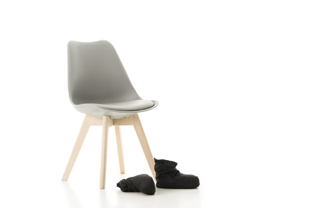 isolated chair: Conceptual Elegant Office Chair and a Pair of Back Shoes Isolated on White Background. Emphasizing Copy Space.