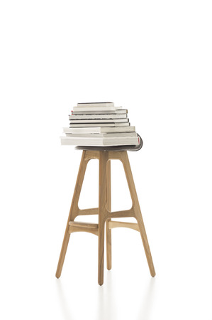 Conceptual Piled Books on Top of Tall Single Chair, with Wooden Legs, Isolated on White Background. Emphasizing Copy Space. Stock Photo