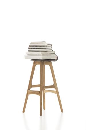 Conceptuele Opgestapelde Boeken op de top van Tall enkele stoel, met houten poten, geïsoleerd op witte achtergrond. Nadruk op Copy Space. Stockfoto