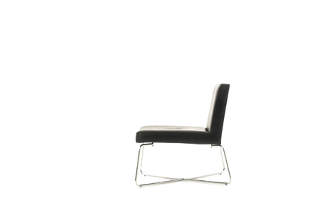 Profile of an elegant modern black chair in a simple classic design with crossed metal legs isolated on white with copyspace