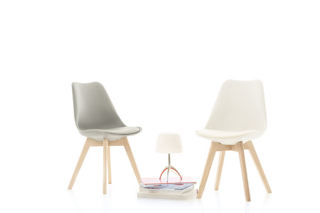 Two stylish modern chairs facing each other with an elegant lamp on a stack of hardcover books between them conceptual of dialogue and discussion, over a white background