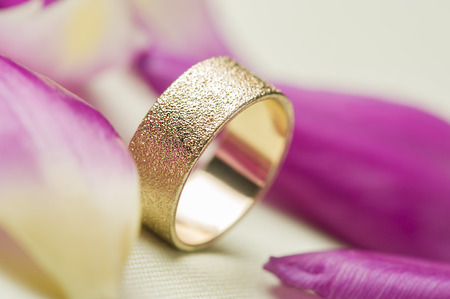 vows: An elegant textured gold wedding band or ring standing upright amongst scattered fresh pink rose petals symbolic of love romance and marriage vows for a lifelong commitment