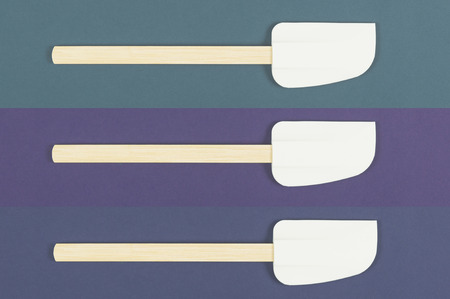 Three kitchen spatulas neatly arranged in a row with aligned heads on blue background in a food preparation and cooking concept, overhead view