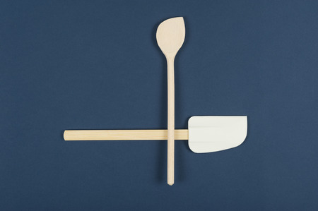 Wooden kitchen spoon and spatula arranged as an asymmetrical cross on a blue background with copyspace in a cookery concept, overhead view