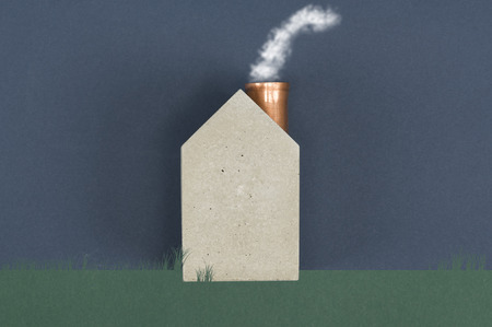 carbon emission: Conceptual house with billowing smoke emitting from the chimney depicting energy efficiency, alternative eco friendly fuel or air pollution and carbon dioxide emission, with copyspace