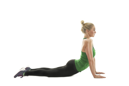 out of body: Athletic young woman working out in a gym doing push-ups, side view with arms extended and body raised isolated on white