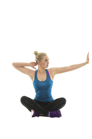 Attractive young woman working out doing yoga stretching exercises with her arms as she sits cross legged in the lotus position on the floor, over white