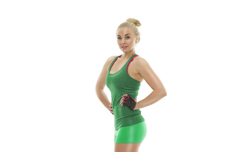Fit healthy attractive young woman with a toned shapely body posing with her hands on her hips in green sportswear showing off her trim waist and physique, on white