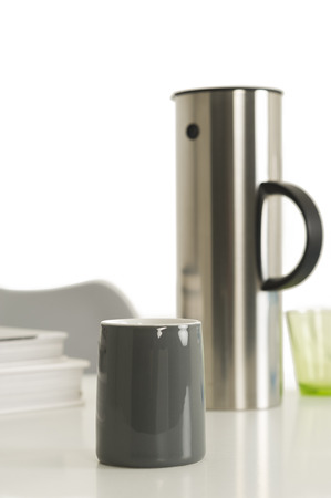dispense: Close up Single Gray Coffee Cup Beside Silver Vacuum Flask on Top of the Table with White Background.