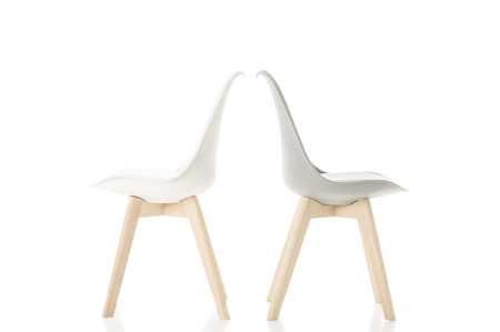 discord: Conceptual Back to Back Elegant White Chairs with Wooden Legs Isolated on White Background