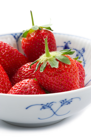 Blue and white porcelain bowl of whole fresh succulent ripe red strawberries with their green stalks attached for a healthy dessert or snack