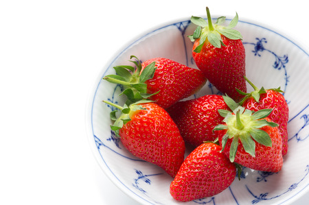 Fresh ripe strawberries, source of antioxidants and vitamin C, in a white bowl with blue decorative pattern, to be served as a healthy snack or dessert, high-angle close-up with copy space on white