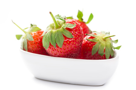 Farm fresh ripe red strawberries with attached green stalks served whole in a plain white bowl as a healthy organic snack or dessert, over white