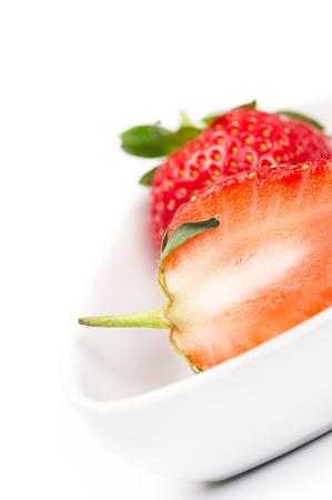 Close-up van de sappige vruchtvlees van een gehalveerde verse rijpe aardbeien in een witte ceramische kom voor gebruik in koken en bakken als een gezonde ingrediënt rijk aan vitamine C