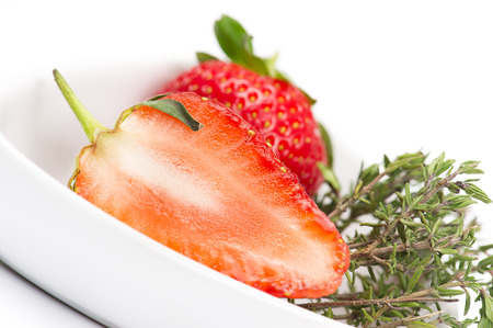 Halved fresh juicy ripe red strawberry showing the structure of the flesh or pulp in a white bowl with a sprig of fresh rosemary to be used as an aromatic flavoring, seasoning and cooking ingredient