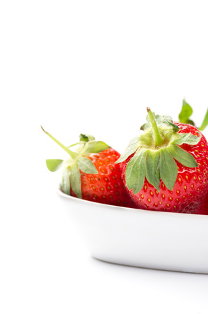 Juicy ripe red whole fresh home grown strawberries in a plain white ceramic bowl with attached green stalks for a healthy finger food snack or cooking and baking ingredient, copyspace on white