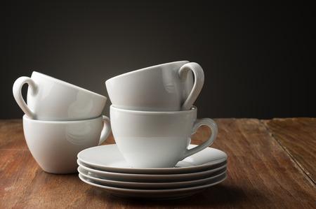 Vier effen wit keramiek koffie of thee kopjes met gestapelde schotels staan klaar op een tafel in een huis, cafetaria of koffie huis aan een aromatisch kopje ontspannende drank serveren