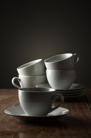 Five plain white ceramic coffee or tea cups on a wooden kitchen counter or table side lit with dramatic lighting with a single cup and saucer in the foreground
