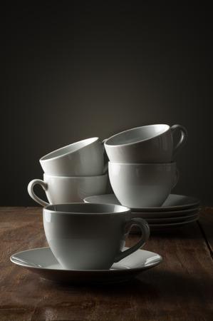 Vijf gewone witte keramische koffie of theekopjes op een houten aanrecht of aan tafelzijde verlicht met dramatische belichting met een enkele kop en schotel op de voorgrond