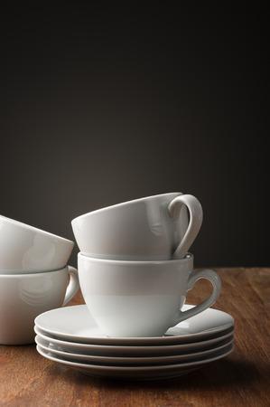 Twee duidelijke witte aardewerk thee of koffie kopjes met schoteltjes gestapeld staan klaar om op een houten tafel voor een ontspannen kop warme drank te dienen, met verticale copyspace