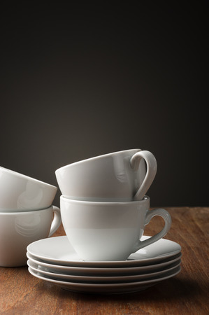 Two plain white pottery tea or coffee cups with stacked saucers standing ready on a wooden table to serve a relaxing cup of hot beverage, with vertical copyspace