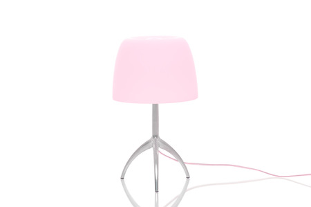 Elegant metal lamp with tripod legs and a pink lampshade standing on a reflective white surface with copyspace Stock Photo