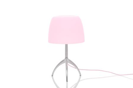 Elegante metalen lamp met statief benen en een roze lampenkap staande op een reflecterende witte oppervlak met copyspace Stockfoto