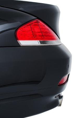 Rood rug staart licht, reflector en bumper van een moderne zwarte auto bekeken close up kant op geïsoleerde op wit