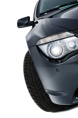 headlights: Shining headlight assembly of a modern black car , frontal view with brand new tyre and protruding wing mirror isolated on white