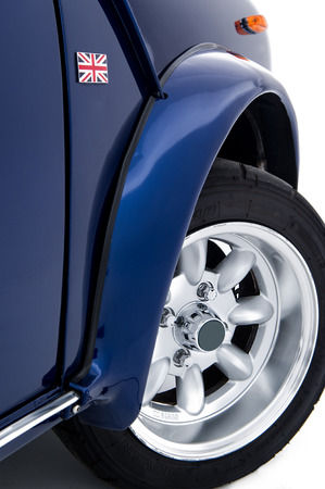 Modern new blue British car in retro style showing the front wheel arch and new spoked alloy wheel on a white background