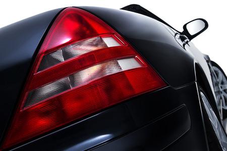 Close-up lage hoek uitzicht op de rode achterlichten licht montage op een moderne zwarte auto met lens detail geïsoleerd op wit