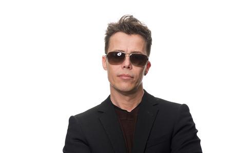 Close-up Ernstige middelbare leeftijd zakenman draagt een zonnebril en kijkt naar de camera, geïsoleerd op een witte achtergrond. Stockfoto
