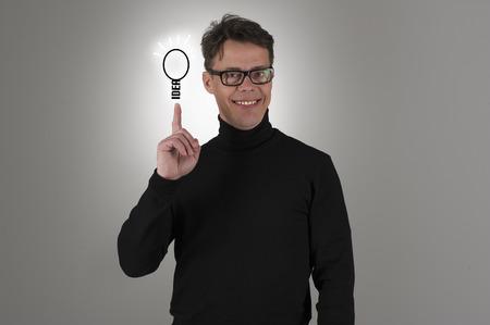 Conceptueel beeld van een knappe vrolijke trots man met zijn brainwave, slim business idee of innovatie met een schets van een stralende gloeilamp in evenwicht op zijn vingertop Stockfoto