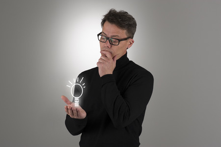 Conceptual image of a handsome man wearing nerdy glasses standing contemplating a bright idea or pondering the solution to a problem with a sketched shining light bulb balanced on his hand